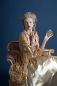 Retro baroque fashion woman wearing gold dress. Holding bottle o — Stock Photo