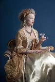Retro baroque fashion woman wearing gold dress. Holding wine gla — Stock Photo