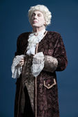 Retro baroque man with white wig standing and looking arrogant.  — Stock Photo