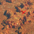 Aerial of red airplane flying over dry red desert landscape. — Stock Photo #49385277