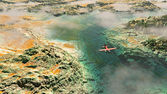 Aerial of red airplane flying over rocky landscape with river an — Stock Photo