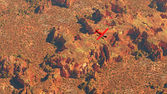 Aerial of red airplane flying over dry red desert landscape. — Stock Photo