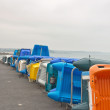 Row of colorful plastic boats on shore. Cloudy sky. Brittany. Fr — Stock Photo #51186103