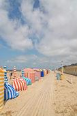 Farbige Schirme am Strand von Deauville mit blau Wolken. — Stockfoto
