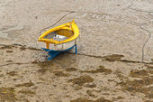 Small boat in harbor of Erquy on sand at ebb-tide with cloudy sk — Stock Photo