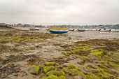 Boats in harbor of Erquy on sand at ebb-tide with cloudy sky. Br — Stock Photo