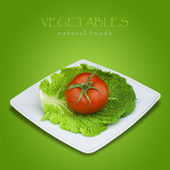 Savoy cabbage and tomato in plate on green background — Stock Photo