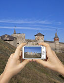 Abstract Camera. Tourist Holds Up Camera at Castle in Kamenets-Podolsky. — Stock Photo