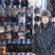 Man sells winter hats. — Stock Photo