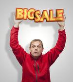 Gran venta. hombre sorprendido sosteniendo la placa 3d. — Foto de Stock