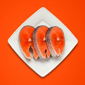 Steak Salmon on plate & red background — Stock Photo