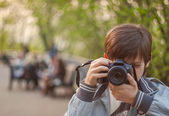 Young photographer clicking photo from camera — Stock Photo