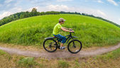 Landscape through fish eye lens with boy racing on bike through green park — Stock Photo