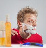 Hombre con crema de afeitar en la cara — Foto de Stock