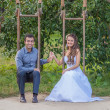 Beautiful young bride and groom on their wedding day in a city park on swing — Stock Photo
