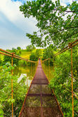 Metal suspension bridge over the river — Stockfoto