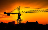 Industrial construction crane and buildings silhouettes over sun at sunrise — Foto Stock