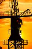 Industrial construction crane  silhouette over sun at sunrise — Foto Stock