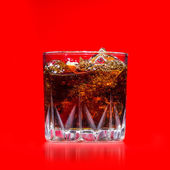Glass with whiskey splash on red background — ストック写真