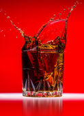 Glass with whiskey splash on red background — 图库照片