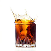 Glass with whiskey splash on white background — Stock Photo