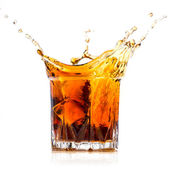 Glass with whiskey splash on white background — ストック写真