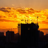 Silhouette of the tower crane on the construction site with city building background — Stock Photo