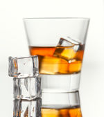 Glass of whiskey with ice, isolated on white background and small depth of field — Stock Photo