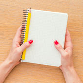 Woman hand holding notebook on wooden background — Stockfoto