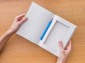 Woman hand holding notebook on wooden background — Stock Photo