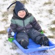 Boy sliding in the snow — Stock Photo