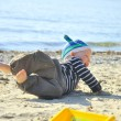 Cute boy playing on a beach — Stock Photo #13179306