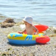 Cute boy rowing a boat on a beach — Stockfoto