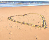 Heart drawn in a sand on a beach and sea — Stok fotoğraf