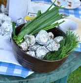 Green onion an potato in a foil in a pot — Stock Photo