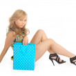 Photo: Beautiful woman with a lot of shopping bags. isolated on white