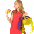 Young beautiful woman with some shopping bags and hamburger isolated on white — Stock Photo