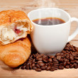 Croissant with coffee and beans on wooden background — Foto de Stock