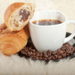 Croissant with coffee and beans on fur background — Stock Photo