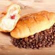 Croissant with coffe beans on wooden background — Foto de Stock