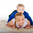 Portrait smiling mother and the child lying at home on the fur — Stock Photo