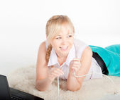 Beautiful young woman with a laptop biting network cable on warm plaid — Stock Photo