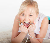 Beautiful crazy young woman biting network cable on warm plaid — Stock Photo