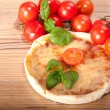 Closeup of pizza with tomatoes, cheese and basil on wooden background — Stock Photo