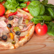 Closeup of pizza with tomatoes, cheese and basil on wooden background — Lizenzfreies Foto