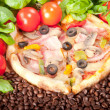Closeup of pizza with coffee beans, tomatoes, cheese and basil - Stock Photo
