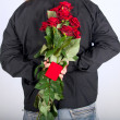 Picture a man holding a red roses and jewely box behind his back — Stock Photo
