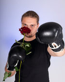 Man in a boxing gloves holding a red rose — Stock Photo