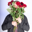 Handsome man offering you a bunch of red roses — Stock Photo