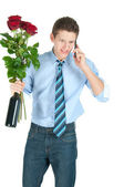 Young business man in blue shirt and tie with bottle of wine, bunch of red roses speaking on a phone — Stock Photo
